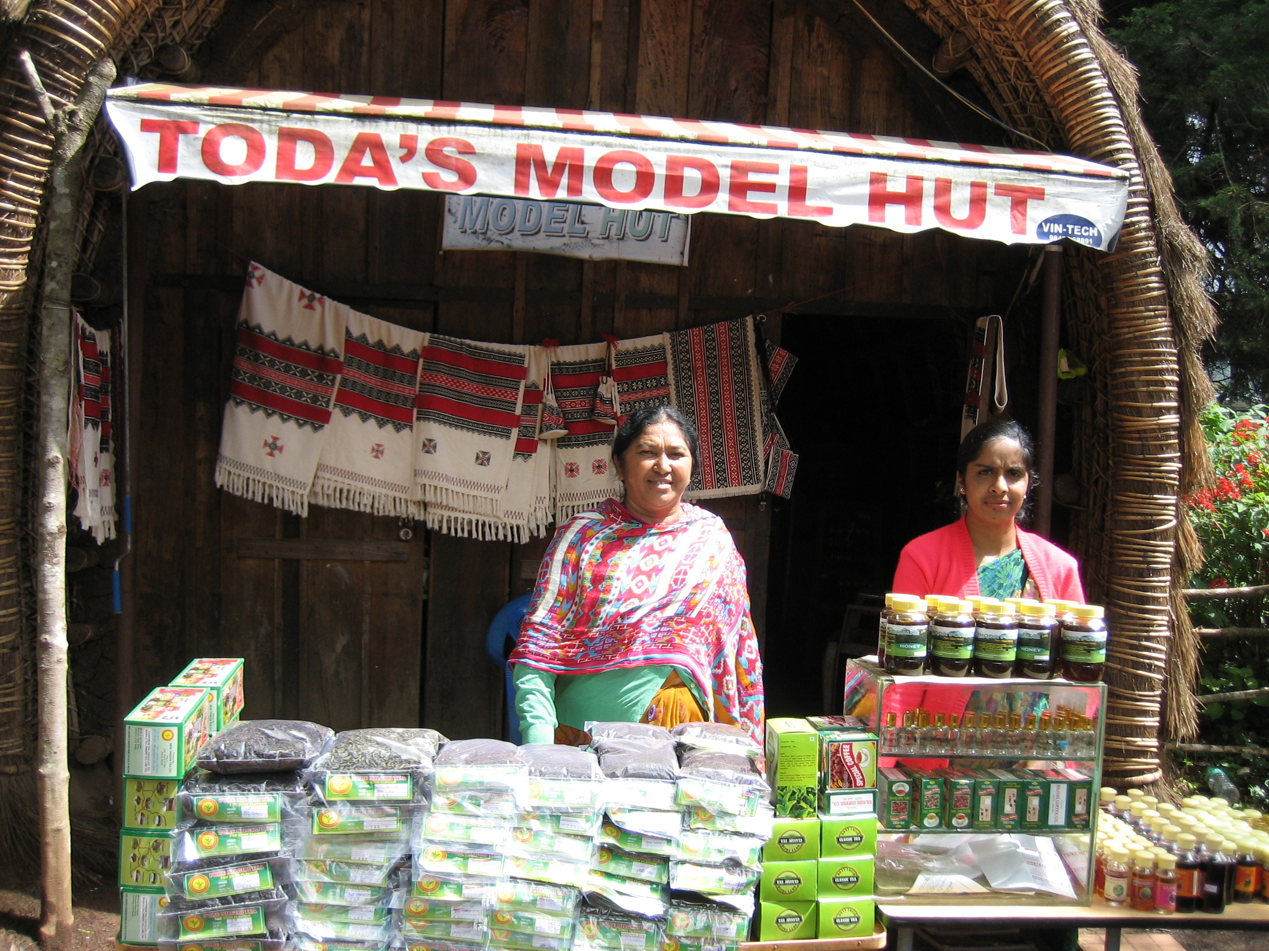 Toda tribal leader Neelasim (left) from the village of Manjakal sells embroidery and goods from her village
