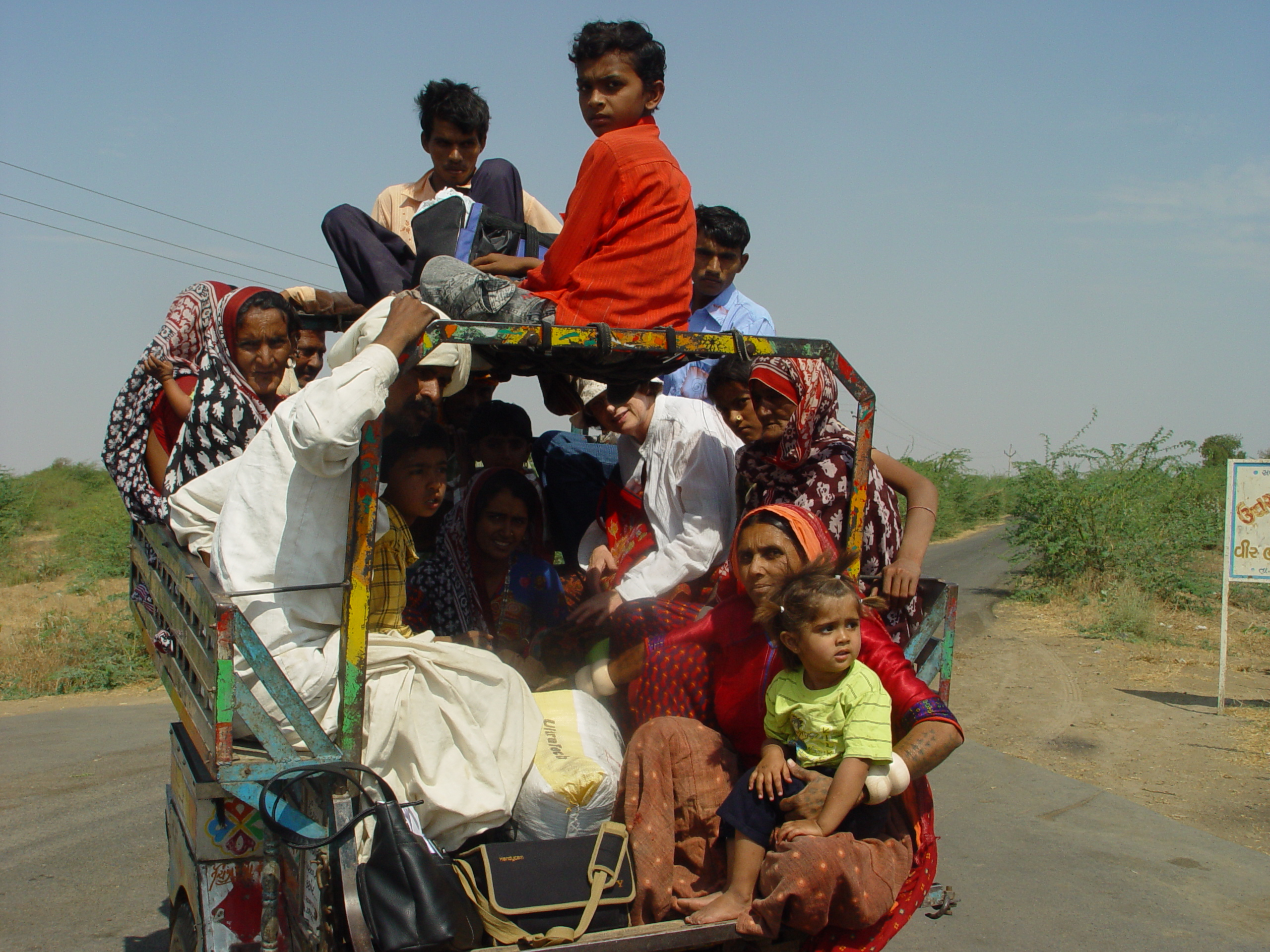 Sheila is squashed into the front in a white shirt, and hanging off the back is Puriben in the red top with her grandchild, en route for a day's work travelling to supervise the work of local embroiderers in the villages she is responsible for.